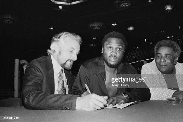 American heavyweight boxer Joe Frazier pictured in centre at a contract signing meeting with boxing promoter Jarvis Astaire on left and trainer Yank...