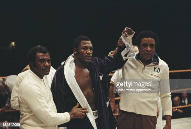 American heavyweight boxer Joe Frazier pictured raising one arm in the air in celebration with his trainer Yank Durham after defeating fellow...