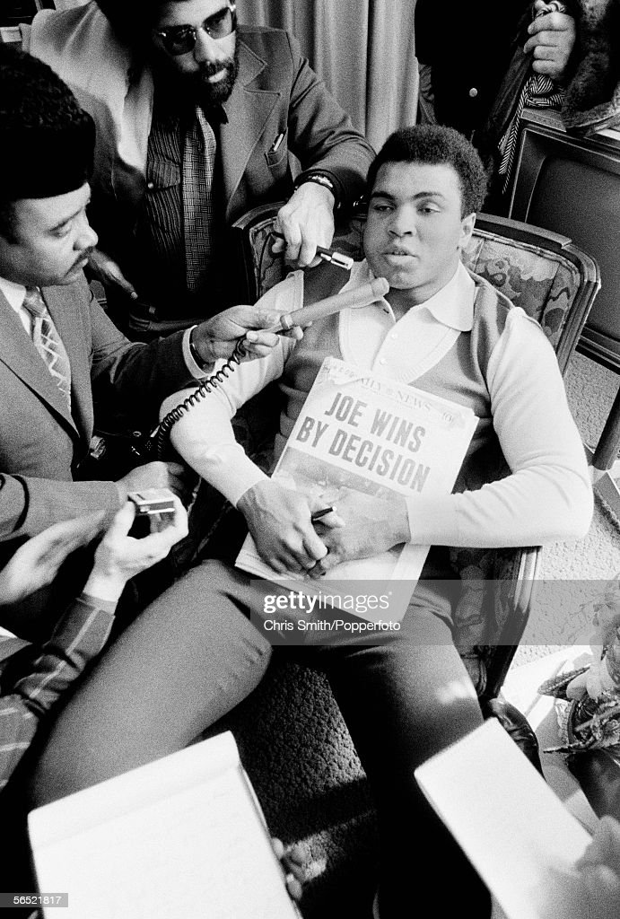 American heavyweight boxer Muhammad Ali clutches a copy of the Daily News with the headline 'Joe Wins By Decision', after losing the title fight against Joe Frazier in New York City, March 1971.