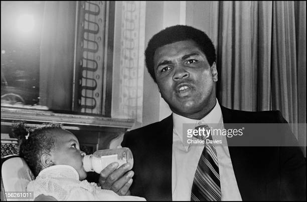 American heavyweight boxer Muhammad Ali feeds his daughter Hana during a press conference at the Cafe Royal London 1977