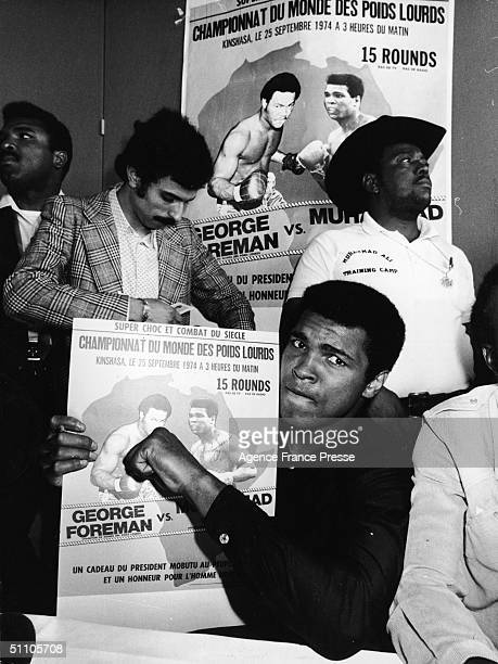 American heavyweight boxer Muhammad Ali makes a fist for the camera while holding a French poster promoting his upcoming fight against George Foreman...