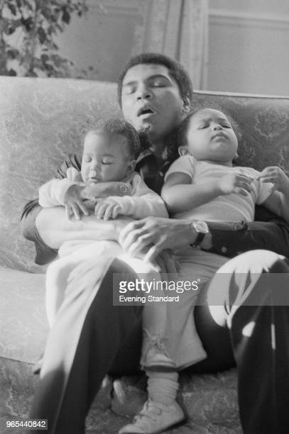 American heavyweight boxer Muhammad Ali takes a nap while babysitting two of his daughters by wife Veronica Porche 9 month old Laila and 2 year old...