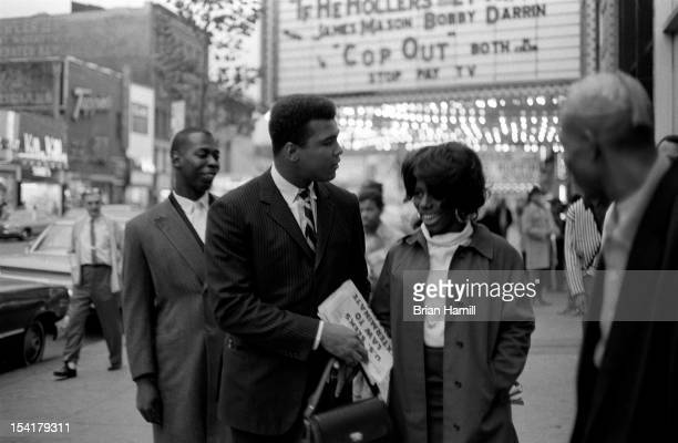 American heavyweight boxer Muhammad Ali talks with an unidentified woman on a sidewalk in Harlem near the Apollo theatre New York New York October 11...