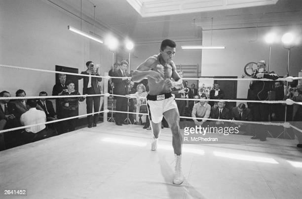 American heavyweight boxer Muhammad Ali throws bare-handed punches in the ring while in training for his fight against Brian London, London, England,...