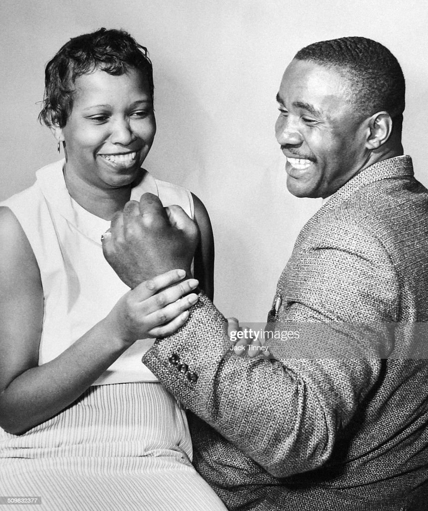 American heavyweight boxer Sonny Liston (?-1970) smiles as his wife, Geraldine (nee Clark), holds his clenched fist, 1969.