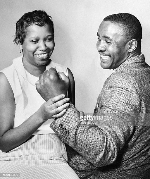 American heavyweight boxer Sonny Liston smiles as his wife Geraldine holds his clenched fist 1969