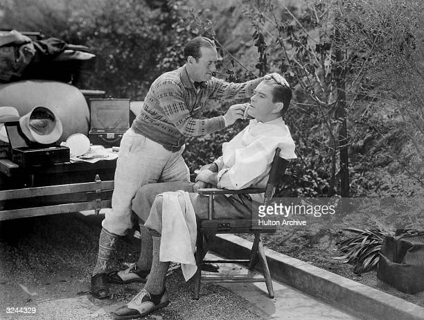 American heavyweight boxing champ Gene Tunney wearing plus fours and oxford shoes sits in a folding chair while his trainer Scotty applies makeup to...