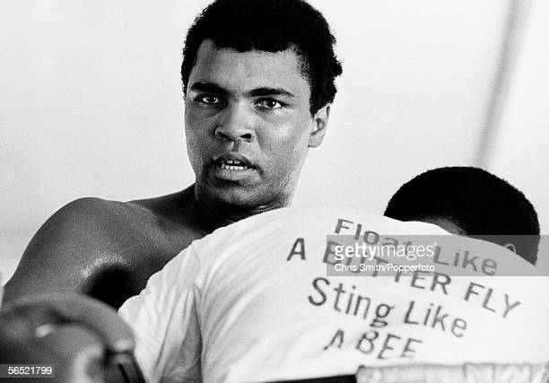 American heavyweight boxing champion Muhammad Ali circa 1970 The man in front of him is wearing a tshirt printed with Ali's motto 'Float like a...