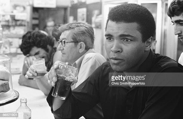 American heavyweight boxing champion Muhammad Ali drinks a CocaCola at the counter of a diner in Miami Beach 26th February 1971