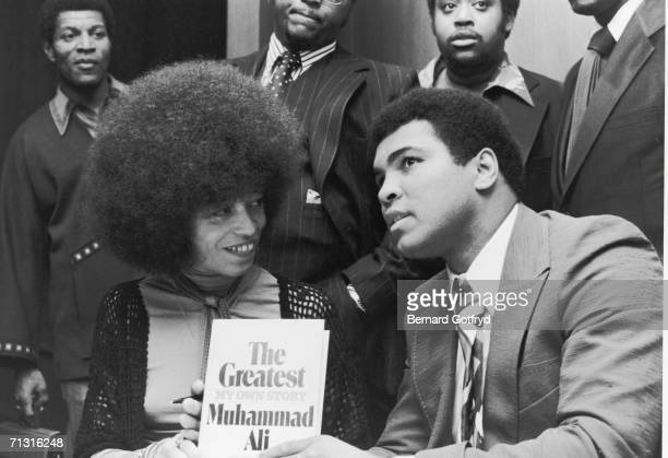 American heavyweight boxing champion of the world Muhammad Ali with Black Power activist Angela Davis. He holds a copy of his autobiography, 'The...