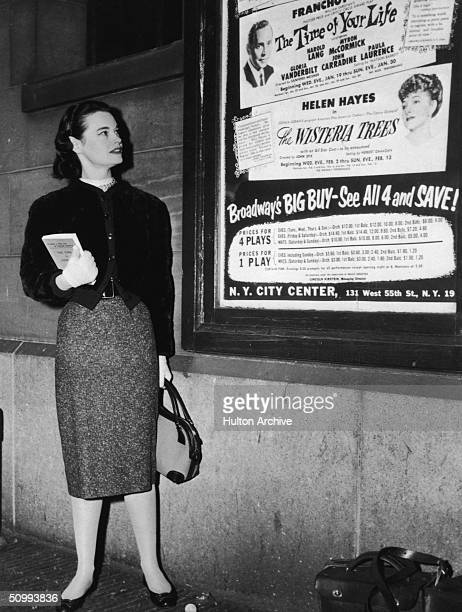 American heiress and actress Gloria Vanderbilt stands next to a poster advertising several plays, including 'The Time of Your Life' which features...
