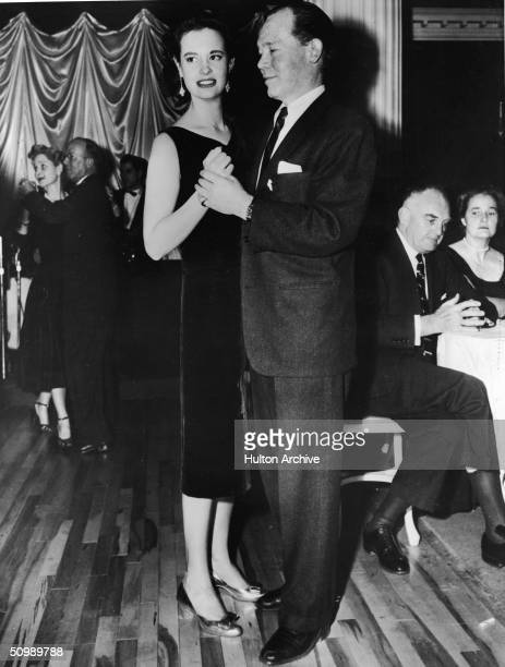American heiress and designer Gloria Vanderbilt dances with American stage and film actor Myron McCormick on a wooden floor as other people dance or...