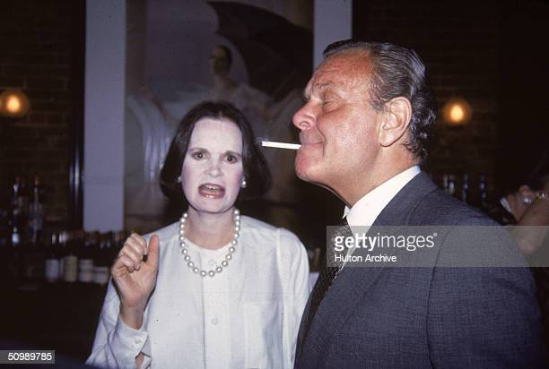 American heiress and designer Gloria Vanderbilt talks to American fashion designer Bill Blass as he smokes a cigarette at the bar at Mortimer's for a...
