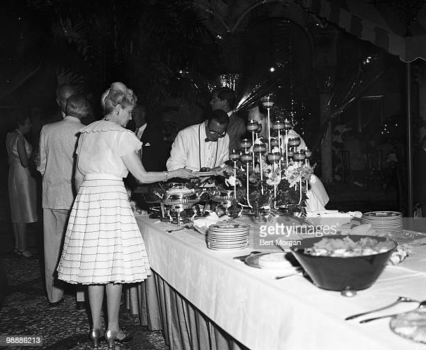 American heiress businesswoman and philanthropist Marjorie Merriweather Post fills her plate during a buffetstyle meal at a party on the tiled garden...