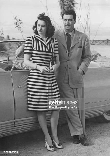 American heiress Gloria Vanderbilt posed with her husband, agent and producer Pat DiCicco beside their car on honeymoon at the El Rancho Hotel near...