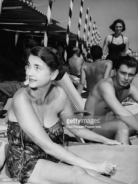 American heiress to the Woolworth estate Barbara Hutton wears a bathing suit as she relaxes at the Lido with her son Lance Reventlow in Venice during...