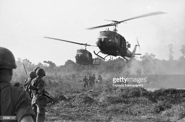 American helicopters hover above armed US soldiers preparing to lift them from combat back to their base in Tay Ninh