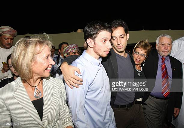 American hiker Josh Fattal is hugged by his brother alongside his mother and father after stepping off an Omani Royal Air Force plane on September 21...