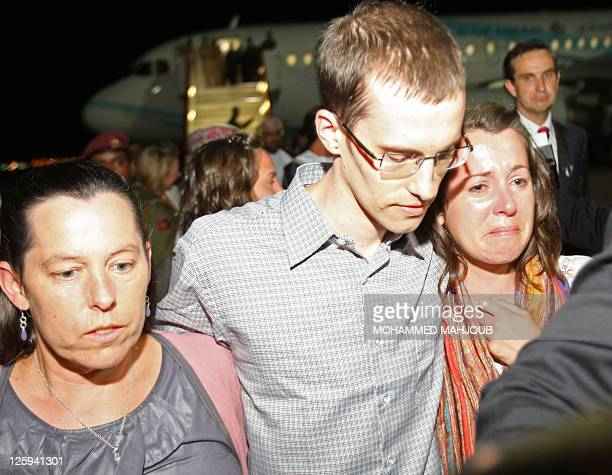 American hiker Shane Bauer is embraced by his mother and sister after stepping off an Omani Royal Air Force plane on September 21 2011 in Muscat Oman...