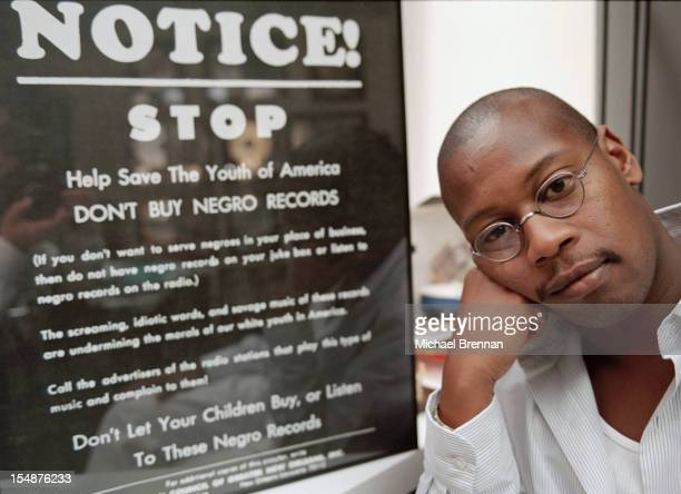 American hip hop artist Andre Harrell founder of record label Uptown Records New York City 1996 Next to him is a sign reading 'Notice Stop Help save...