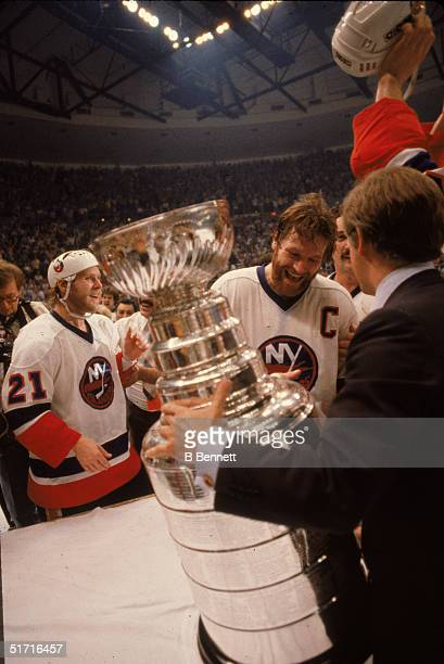 American hockey executive John Ziegler, president of the NHL, awards the Stanley Cup to Canadian hockey player Denis Potvin, captain of the New York...