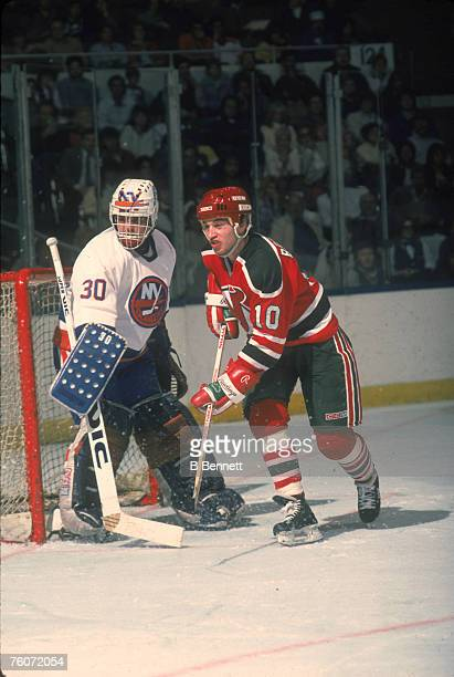 American hockey player Aaron Broten of the New Jersey Devils jostles with Canadian goalkeeper Kelly Hrudey of the New York Islanders in front of the...