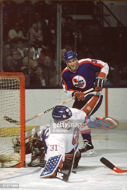 American hockey player Dave Silk forward for the Winnipeg Jets looks for a rebound against goalie Billy Smith of the NY Islanders at Nassau Coliseum...