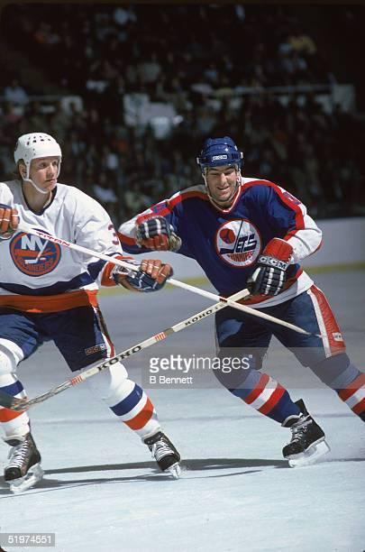 American hockey player Dave Silk forward for the Winnipeg Jets battles defenseman Tomas Jonsson of the NY Islanders at Nassau Coliseum Uniondale New...