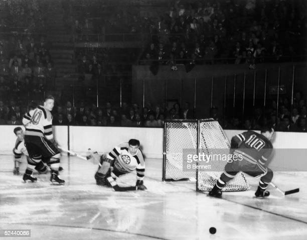 American hockey player Frank Brimsek goalkeeper for the Boston Bruins lunges as he makes a save from a shot by the New York Rangers' Edgar Laprade...