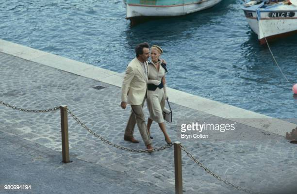 American Hollywood actress Cheryl Ladd playing Grace Kelly and actor Alejandro Rey playing Oleg Cassini walk arm in arm along a quayside in France as...