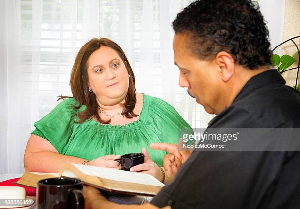 American housewife listening to Christian evangelist reading the Bible