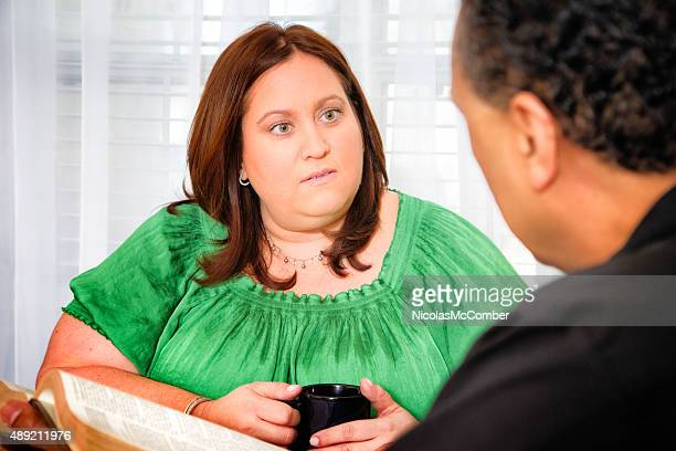 American housewife listens attentively while pastor reads her Bible