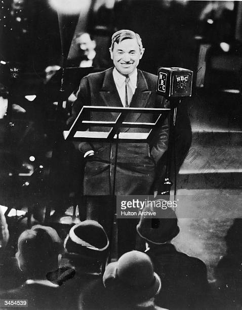 American humorist Will Rogers smiles while standing in front of an audience for his regular radio broadcast 1930s