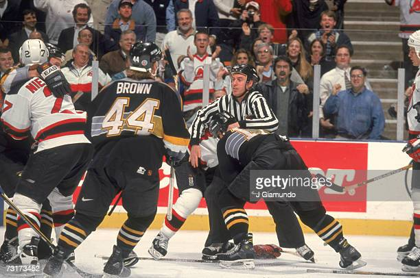 American ice hockey linesman Pat Dapuzzo breaks up a fight during a game between the New Jersey Devils and the Pittsburgh Penguins January 1998