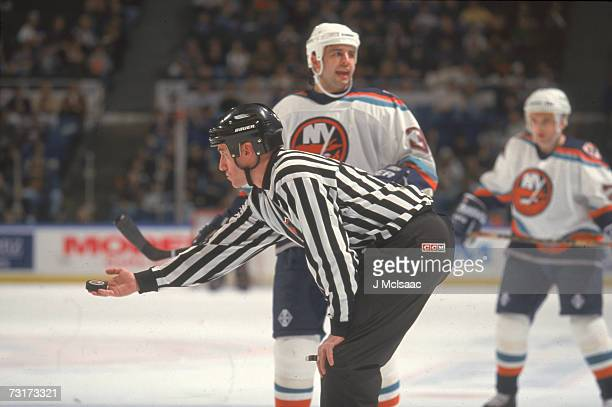 American ice hockey linesman Pat Dapuzzo prepares to drop the puck during a game involving the New York Islanders January 1998