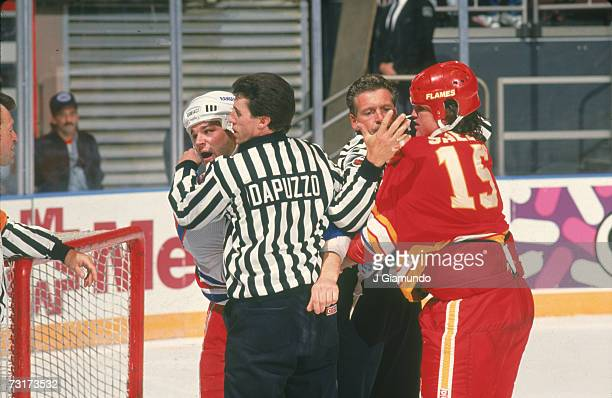 American ice hockey linesman Pat Dapuzzo restrains Kris King of the New York Rangers while a second linesman holds onto Neil Sheehy of the Calgary...