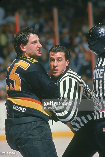 American ice hockey linesman Pat Dapuzzo restrains Rich Sutter of the Vancouver Canucks March 1990