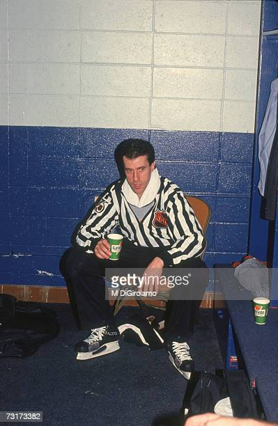 American ice hockey linesman Pat Dapuzzo sits on a bench in the locker room and drinks from a paper cup December 1991
