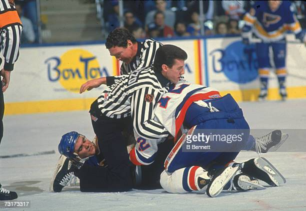 American ice hockey linesmen Pat Dapuzzo and Kevin Collins break up a fight during a match between the St Louis Blues and the New York Islanders 1980s
