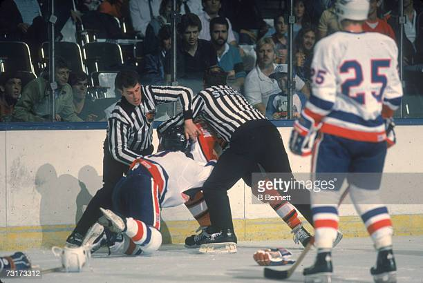 American ice hockey linesmen Pat Dapuzzo and Leon Stickle break up a fight during a game between the New York Islanders and the Philadelphia Flyers...