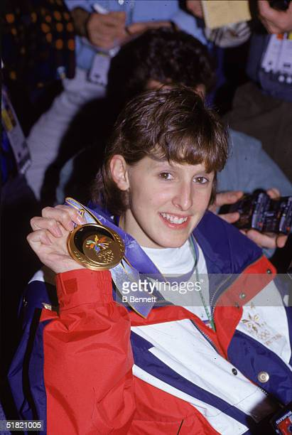 American ice hockey player Cammi Granato of the United States women's hockey team smiles as she holds up her gold medal following a championship...