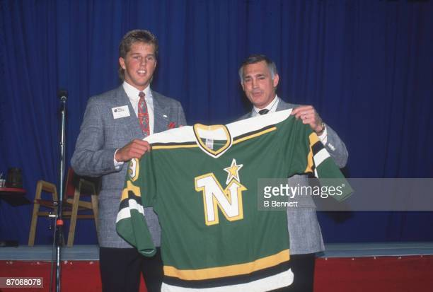 American ice hockey player Mike Modano poses with Lou Nanne coach of the Minnesota North Stars as they hold a North Stars jersey following Modano's...