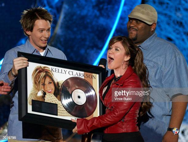 American Idol finalists Clay Aiken and Ruben Studdard present Kelly Clarkson with a platinum record plaque for her first album during the show's...