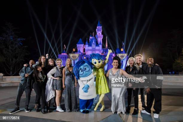 American Idol Top 10 Contestants pose with Joy and Sadness from the Pixar film Inside Out following a performance in front of Sleeping Beauty Castle...