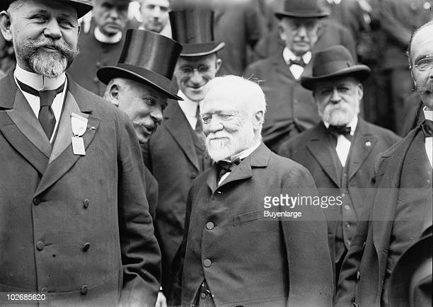 American industrialist and philanthropist Andrew Carnegie smiles as he stands with unidentified others 1913