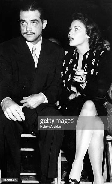 American industrialist, aviator, and film producer Howard Hughes sits at an unidentified event with American actress and screen icon Ava Gardner ,...