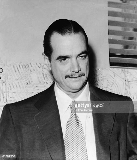 American industrialist, aviator, and film producer Howard Hughes stands in front of a wall-mounted street map, mid 1946.