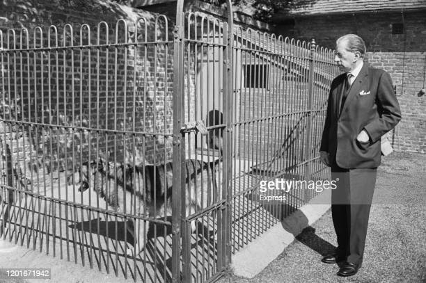 American industrialist J Paul Getty inspecting a caged dog 20th June 1965