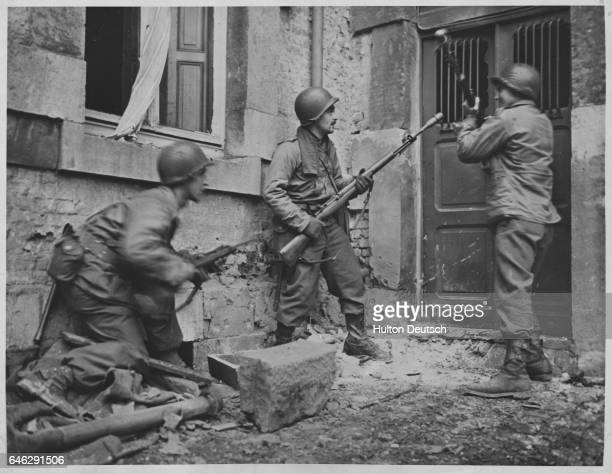 American infantrymen break down door of a house in a Belgian town occupied until recently by German troops ca 1945