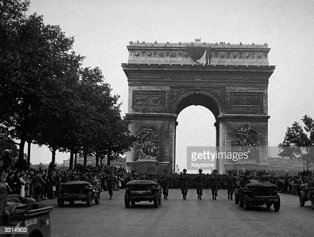 American infantrymen follow their jeeps in the triumphant parade down the Champs Elysees celebrating the Liberation of Paris The Arc de Triomphe can...